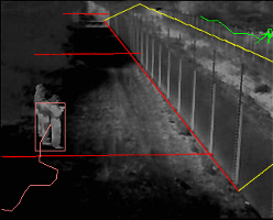 A thermal image of someone standing next to the perimeter fence